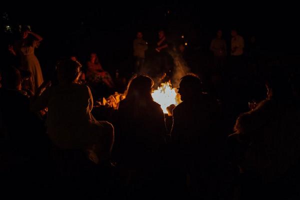 Wedding guests sitting around campfire