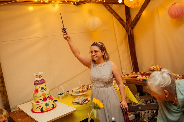 Lady holding knife in the air for cake cutting