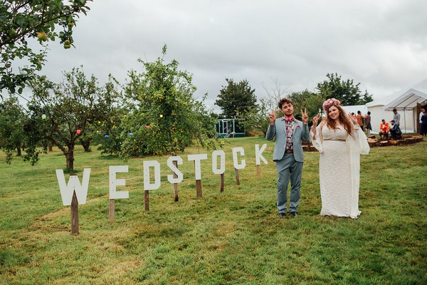 Bride and groom standing next to Wedstock sign