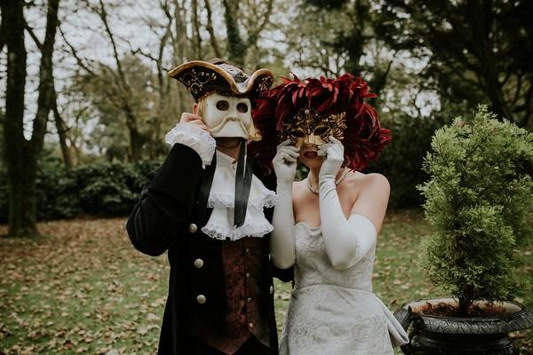 Bride and groom in Georgian outfits wearing Venetian masks