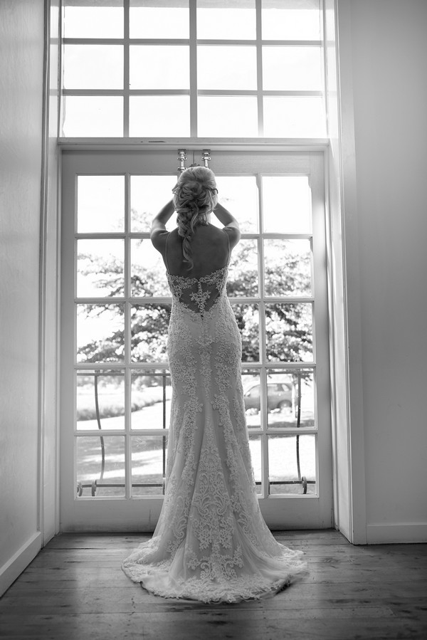 Bride standing looking out of window