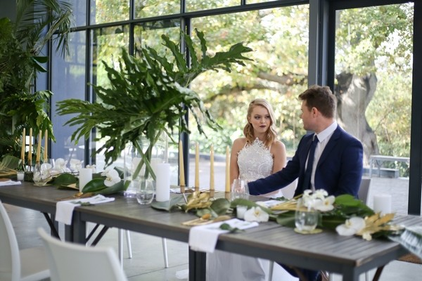 Bride and groom sitting at wedding table with botanical styling