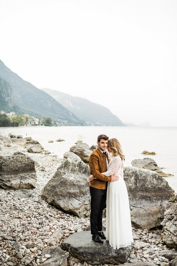 Bride and groom by rocks at Lake Como