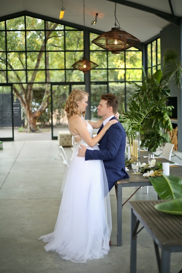Groom sitting on edge of table facing bride