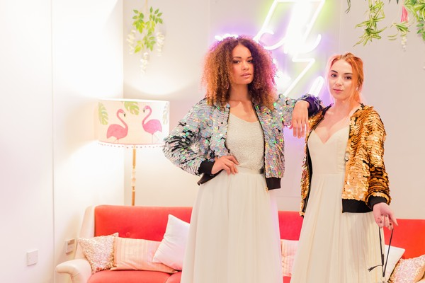 Two brides wearing sequin bomber jackets