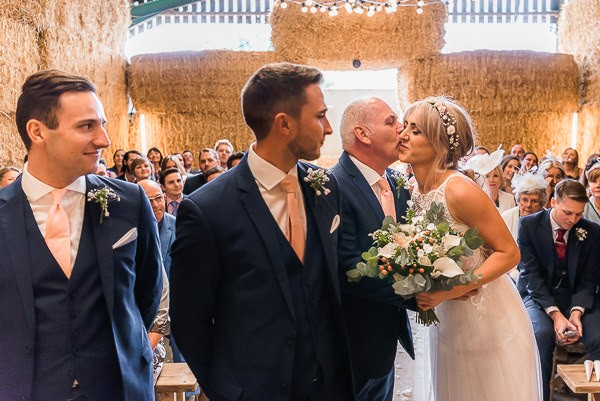 Father kissing bride at altar