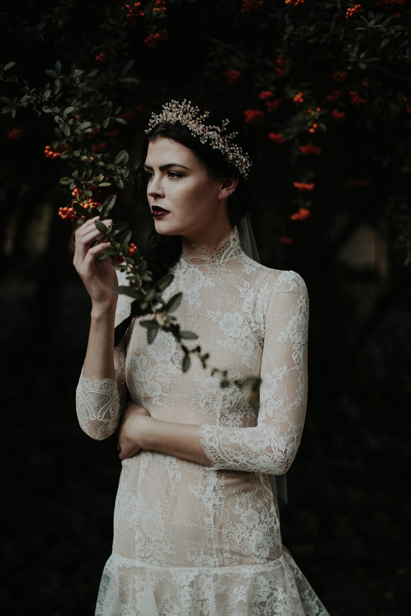 Bride with lace detailed dress standing under tree
