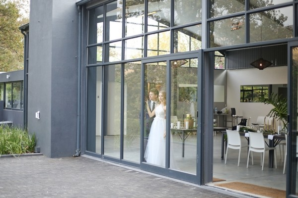 Bride and groom at window of The Conservatory Franschhoek