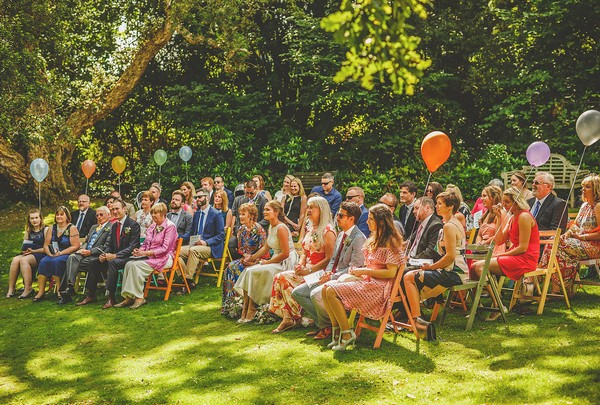 Wedding guests sitting outside for ceremony at Colehayes Park
