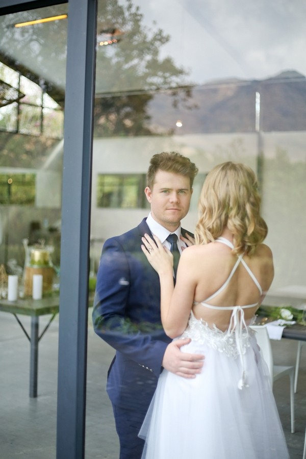 Bride and groom behind window of The Conservatory Franschhoek