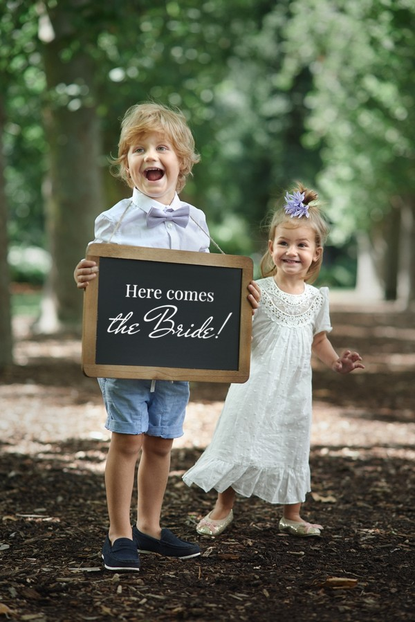 Pageboy holding 'here comes the bride' sign