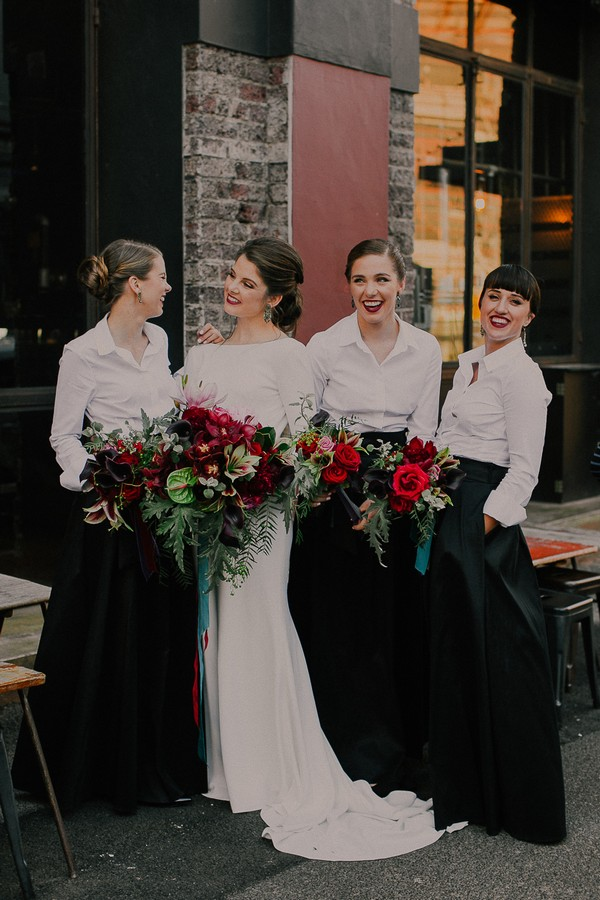 Bride with bridesmaids in white shirts and black skirts