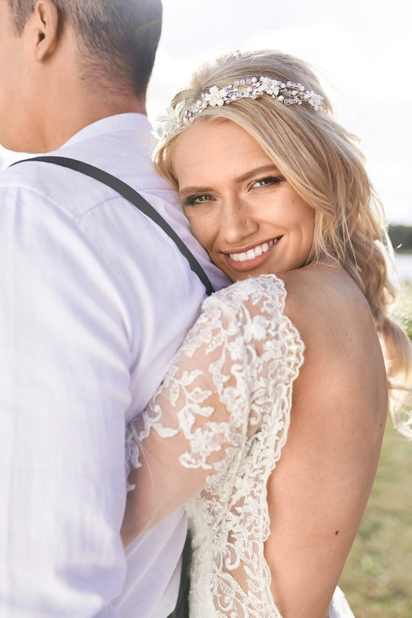 Bride with open back dress hugging groom from behind