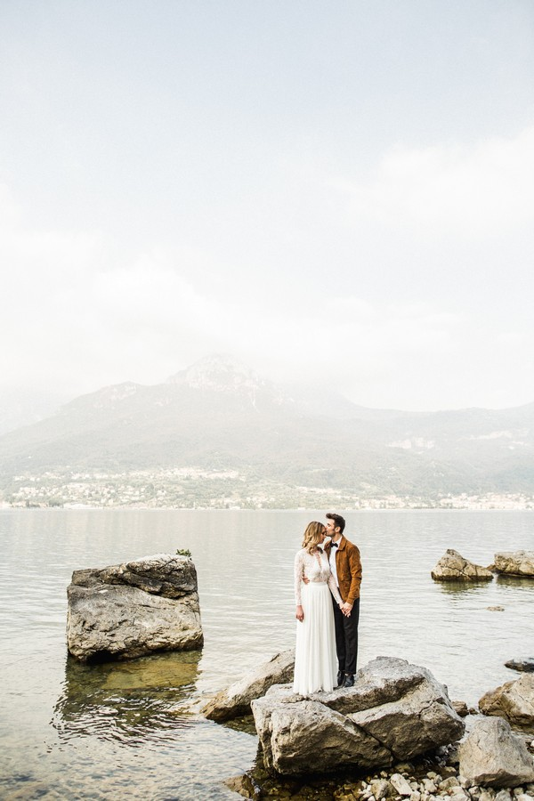 Bride and groom standing on rock at Lake Como