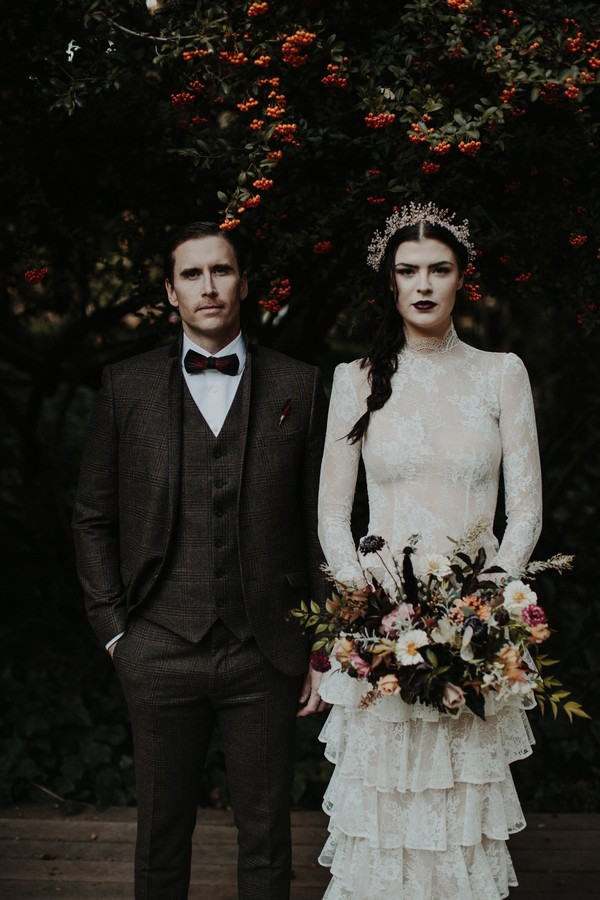 Vintage bride and groom standing next to each other under tree