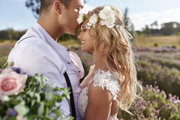Groom kissing boho bride on head