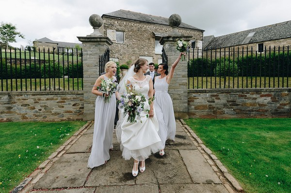 Bridesmaid pulling funny face and raises bouquet in air as she walks with bride - Picture by Michael Marker Photography