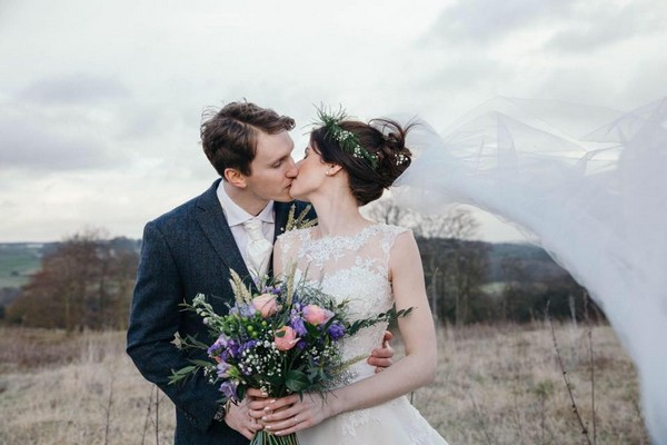 Bride and groom kissing at bride's veil blows in wind - Picture by Rosie Images Photography