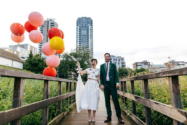 Bride and groom standing on bridge with bride holding balloons - Picture by Jordanna Marston Photography