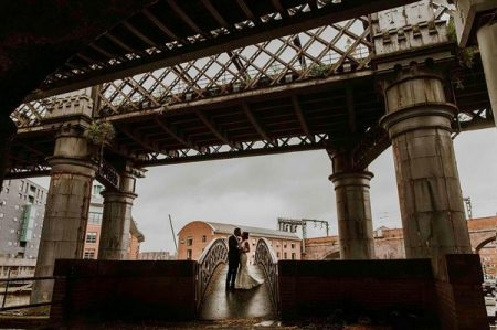 Bride and groom standing on a bridge under a bridge - Picture by Maddie Farris Photography