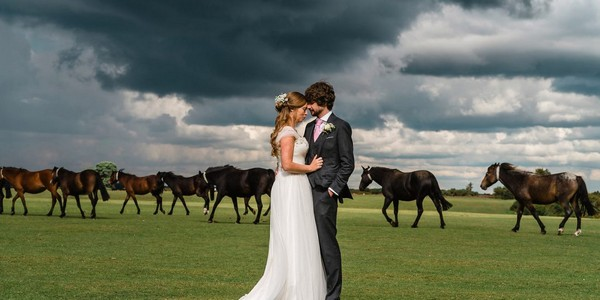 Bride and groom with horses and black clouds in background - Picture by Lemontree Photography