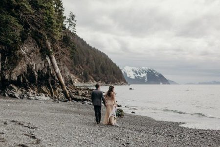 Bride and groom walking across pebble beach with mountain in background - Picture by Kristian Irey Photography