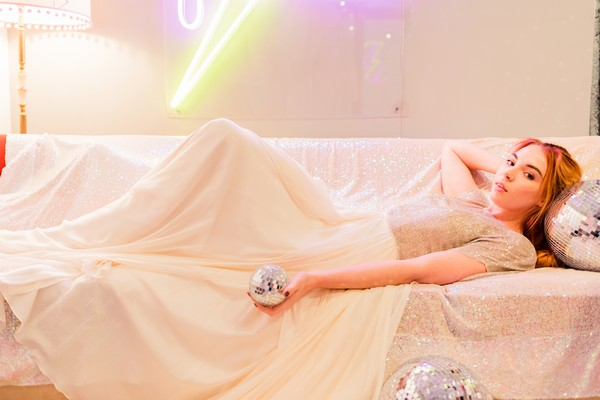 Bride laying on couch holding small disco ball