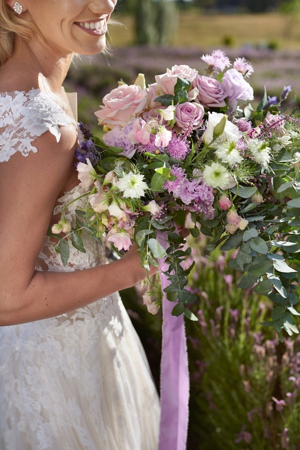 Bride holding lilac and lavender bouquet