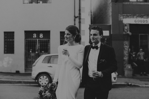 Bride and groom walking holding coffee cups