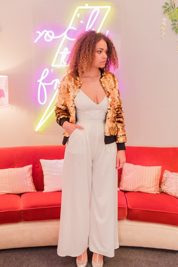 Bride wearing jumpsuit and gold sequin bomber jacket