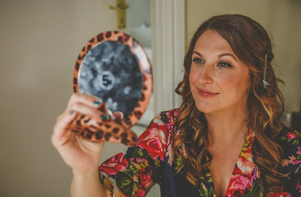 Bride looking at wedding make-up in mirror
