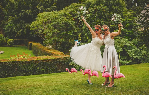 Bride and bridesmaid wearing sunglasses and holding bouquets in the air