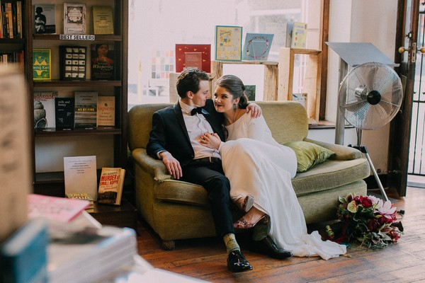 Bride and groom sitting on couch in book shop