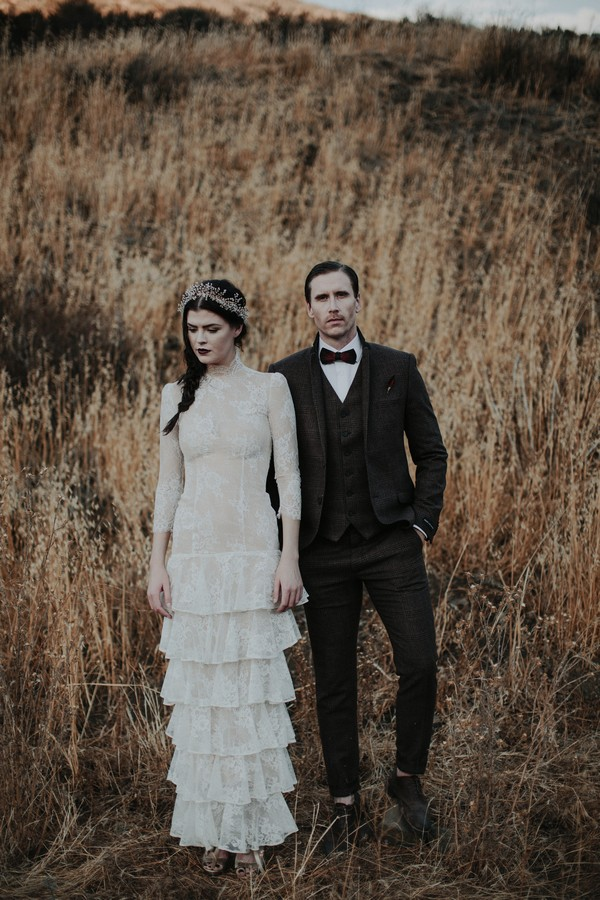 Bride and groom standing by long grass