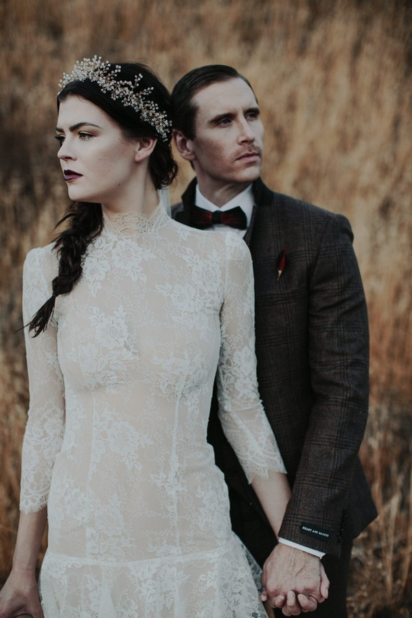 Groom standing behind bride holding her hand