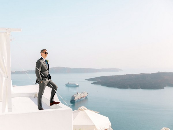 Groom standing with sea in background