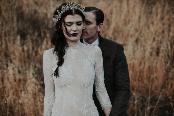 Groom standing behind bride