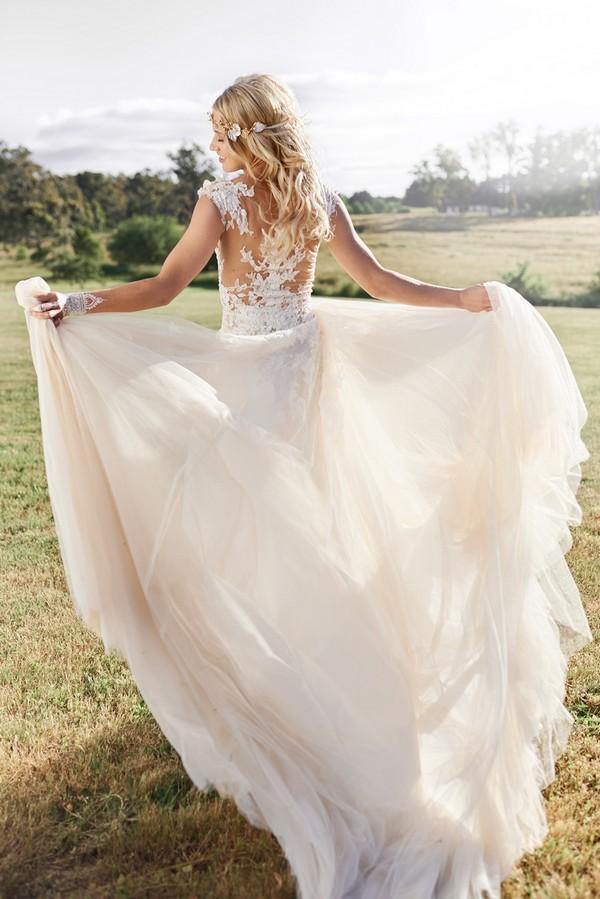 Boho bride holding out skirt on wedding dress