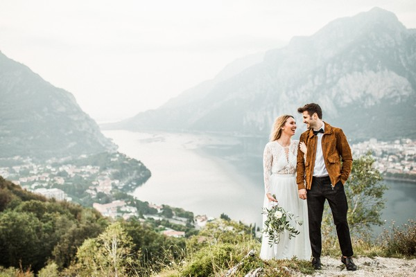 Bride and groom holding hands with Lake Como in background