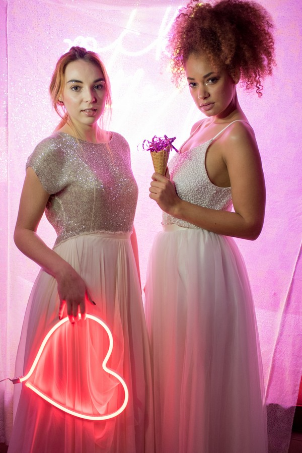 Two brides holding neon heart