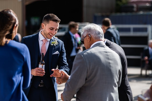 Groom showing guest his wedding ring
