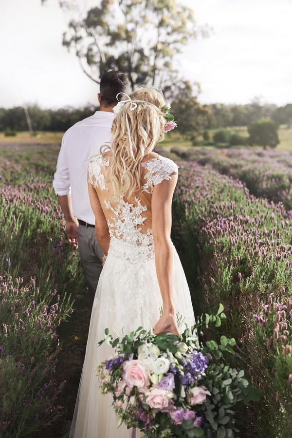 Bride and groom walking through field of lavender