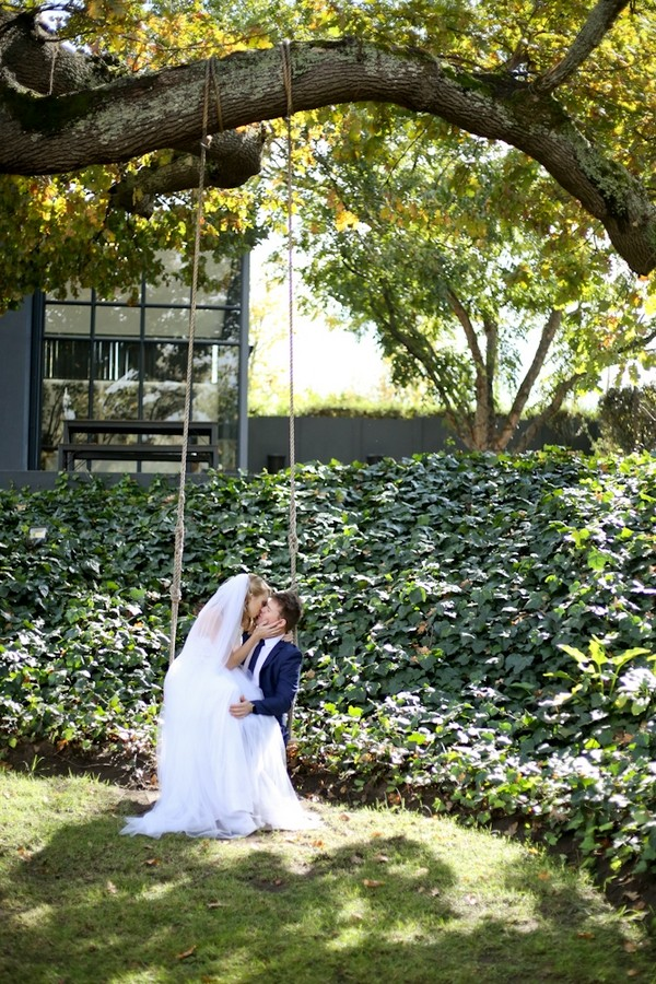 Bride and groom sitting on swing in grounds of The Conservatory Franschhoek