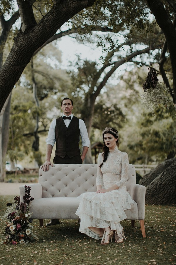 Groom standing behind bride sitting on couch