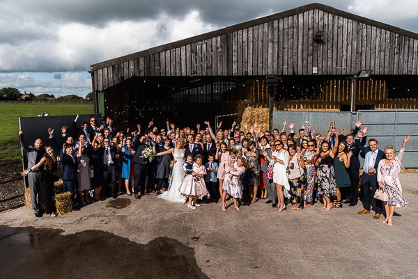 Wedding guests outside cow shed