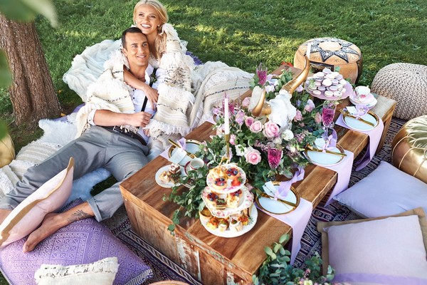 Bride and groom laying on cushions by outdoor wedding table