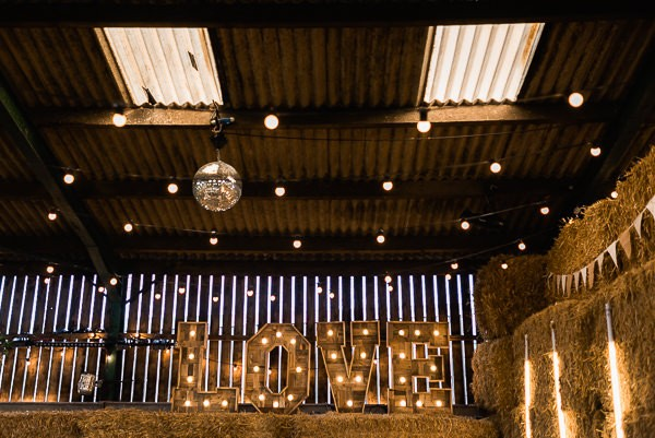 Illuminate love letters and disco ball in cow shed