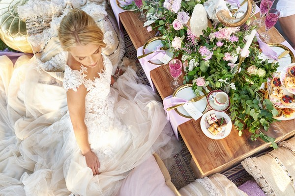 Bride sitting by outdoor wedding table