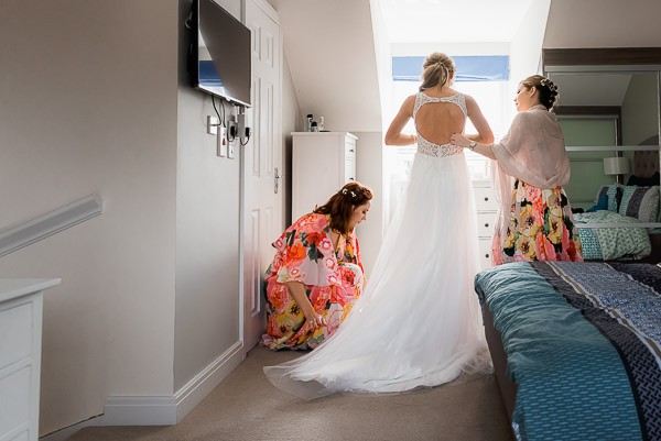 Bridesmaids helping bride with wedding dress