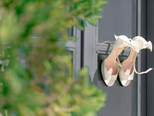 Wedding shoes hanging on door
